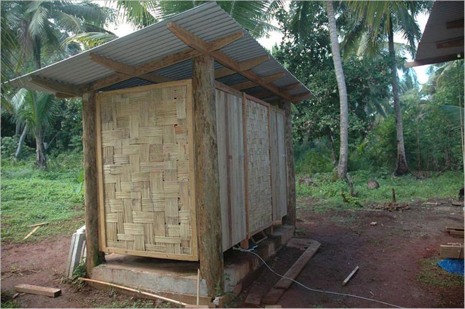 Hier sieht man das Badehäuschen. Es hat auch ein Blechdach und Wände aus Bambusmatten