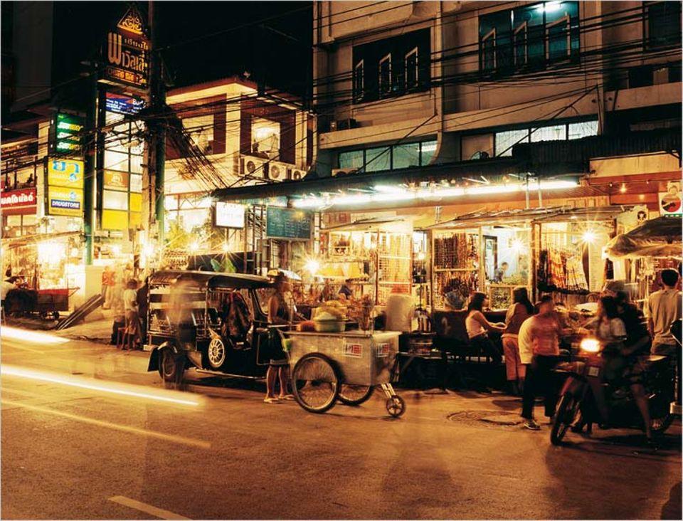 Wenn die Sonne untergegangen ist und die Hitze des Tages weicht, verwandeln sich die Straßen in Chiang Mai in pulsierende Lebensadern. Marktstände, mobile Garküchen, Shops und Restaurants mit dazugehörigen Massageplätzen locken Einheimische und Durchreisende gleichermaßen