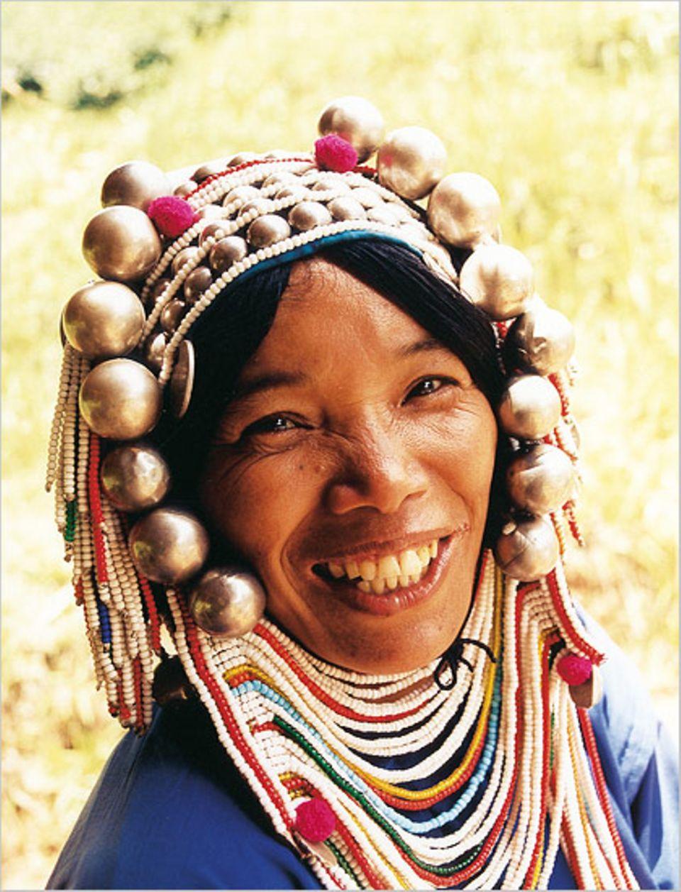 Die Frau vom Bergvolk der Akha trägt auch bei der Feldarbeit ihren traditionellen Schmuck