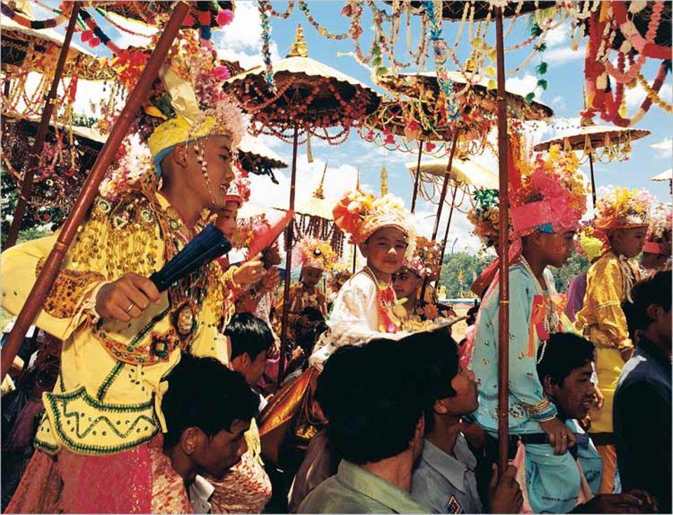 In Mae Lana sind wir Zeugen eines buddhistischen Fests: Die herausgeputzten Novizen werden vor ihrem Eintritt ins Kloster durch das Dorf getragen. Am Ende der Zeremonie tauschen die Kinder ihr Festtagsgewand gegen die traditionelle orangefarbene Kutte der Mönche