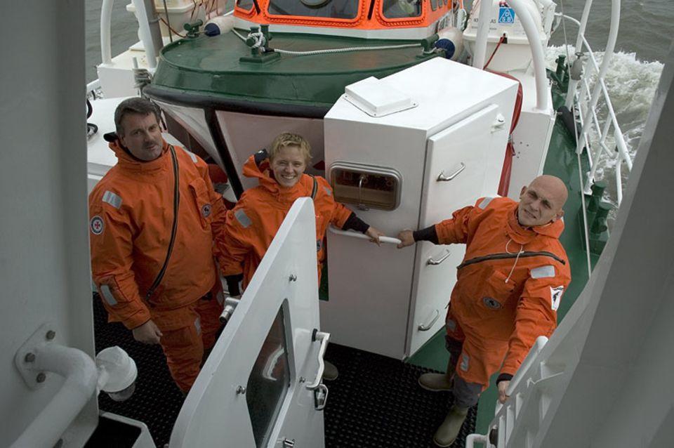 Noch grinst Sina in die Kamera. Wenige Sekunden später springt sie mit Seenotretter Jochen Eicken (rechts) in die Nordsee. Sein Kollege Michael Ulrichs (links) überwacht die Übung von Bord aus