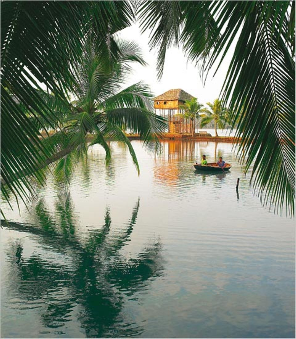 In den Valiyaparamba Backwaters, einem Labyrinth aus Kanälen, Flüssen und Lagunen, sind Boote das praktischste Verkehrsmittel. Die Pfahlhütte im Hintergrund gehört zu den fünf Unterkünften des Resorts