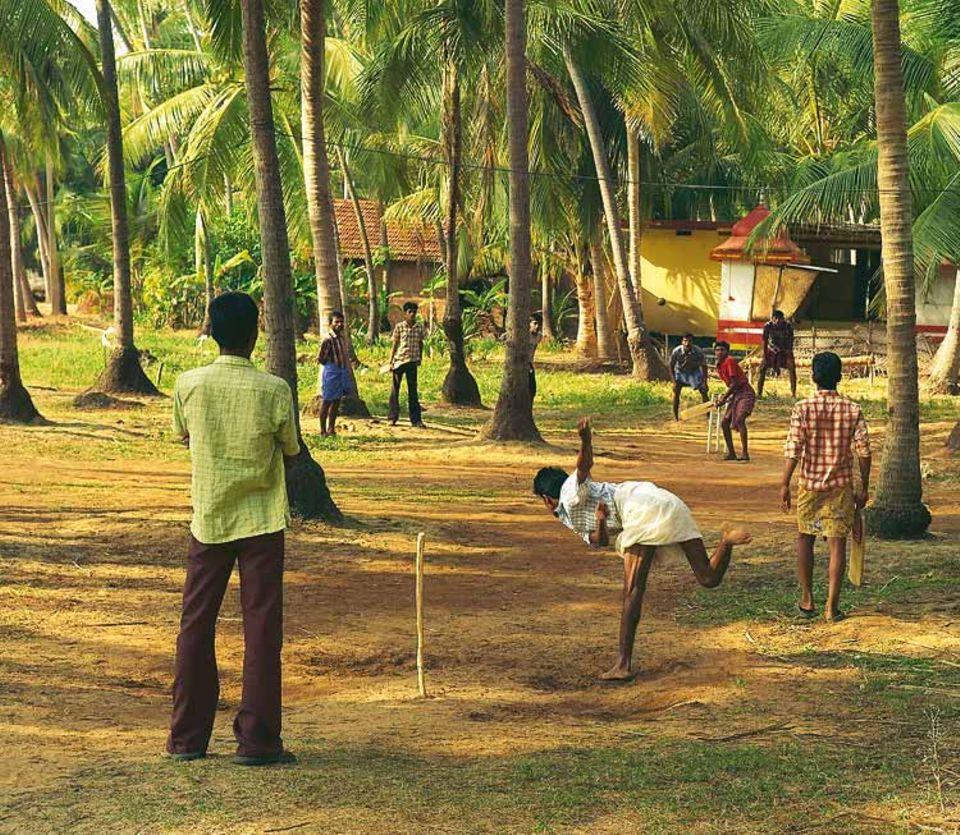 Cricket, ein Erbe der britischen Kolonialzeit, ist die beliebteste Sportart Indiens - auch bei den Jugendlichen der Insel Thekkekadu. Hinter dem Spielfeld: der gelbe und orangefarbene Tempel des Gottes Palichon Kave