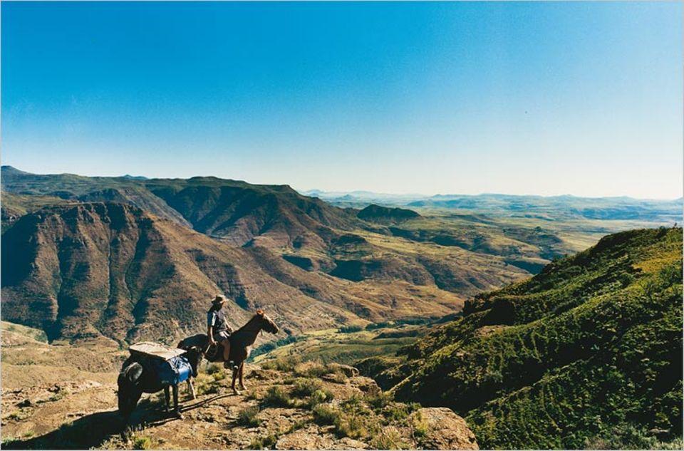 Blick auf eine Landschaft ohne Straßen. Pferde tragen den Reisenden und das Gepäck über schmale Pfade durch das Thaba-Putsoa-Gebirge