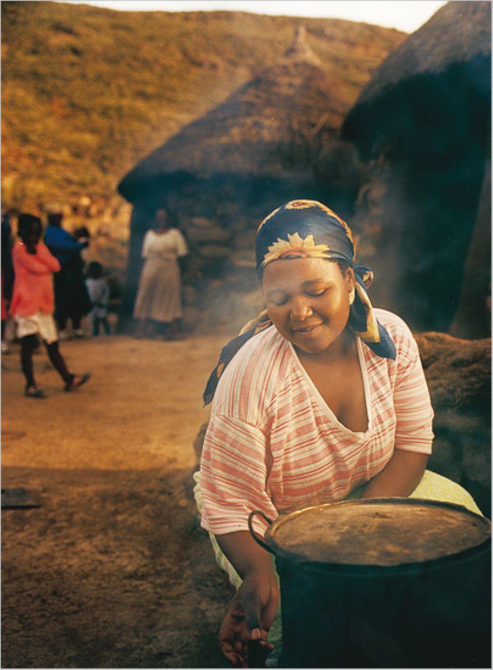 Im Dorf Thaba Sekoka kocht eine Frau vor ihrer Hütte das Abendessen für die Familie
