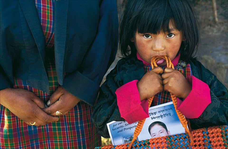 Demokratie in Kinderschuhen: Im Dorf Dhur in Zentralbhutan kommen Mutter und Tochter von einer Wahlveranstaltung, in der Tasche das Bild des Kandidaten