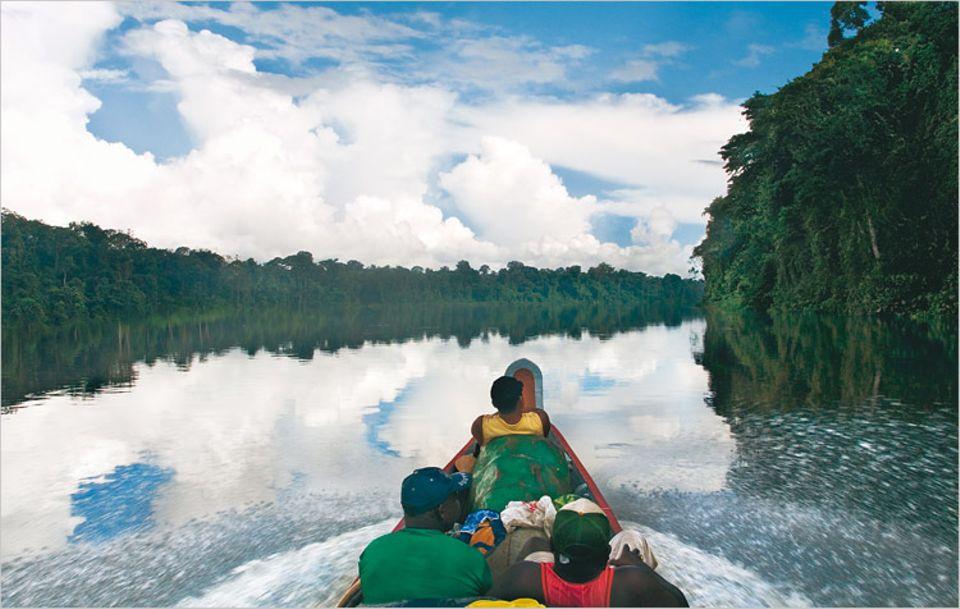 """Passt nicht, gibt's nicht: Chronisch überladen schnellt die """"Vry Libie"""", ein Einbaumboot, den Tapanahony River hinauf - einen bedeutenden Transportweg im Südosten des Landes"""