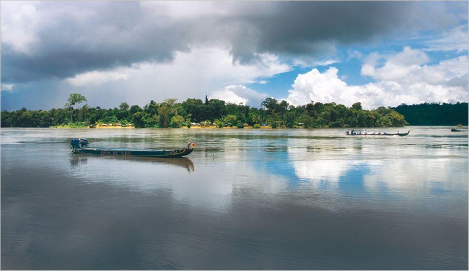 Schmaler Schlepper: Die motorisierten Boote auf dem Marowijne sind mit Touristengruppen und Metallfässern sowie gelegentlich auch mit Baggerschaufeln beladen