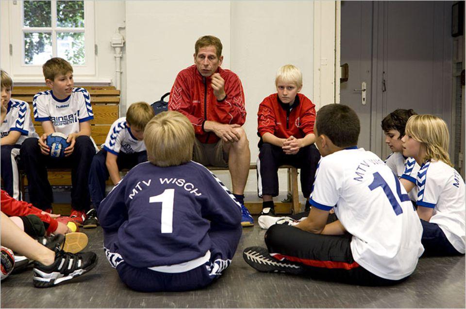 """Vor dem Spiel gibt Trainer Ulrich Pauluschke taktische Tipps und macht seine Spieler heiß: """"Hauen wir die weg?"""" – """"Jaaa!"""""""