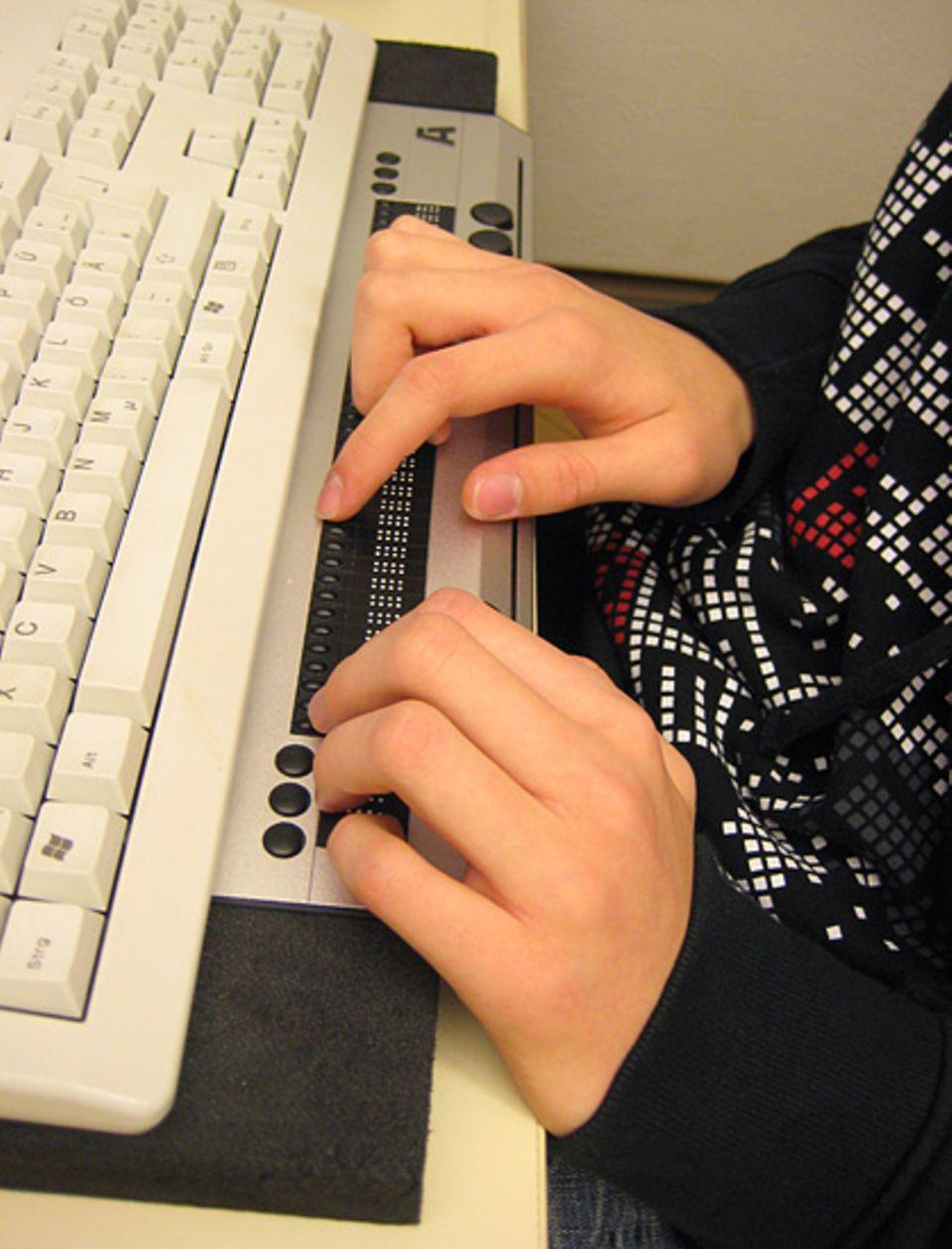 """Lukas' geübte Finger tasten die Braillezeile ab. So kann Lukas allein mit seinem Fingerspitzengefühl """"lesen"""", was der Computer gerade anzeigt."""