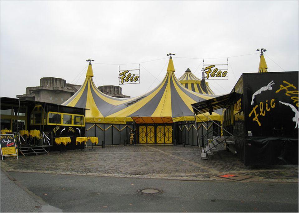 """Hinter dem großen Zirkuszelt des Zirkus FlicFlac stehen die Wohnwagen der Artisten und Angestellten, aber auch das """"fahrende Klassenzimmer"""""""