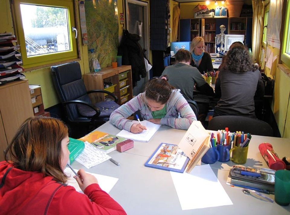 Konzentriert sitzen die Schüler mit ihrer Lehrerin im fahrenden Klassenzimmer über den Aufgaben. Hier werden alle Altersklassen gemeinsam unterrichtet
