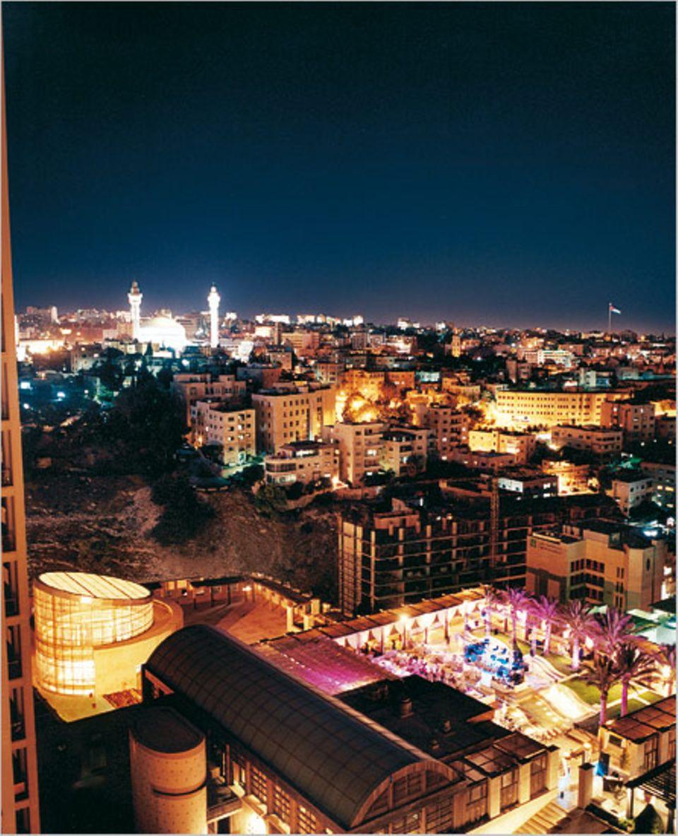 Die Nacht lässt Amman strahlen: Die Minarette der König-Abdullah-Moschee leuchten wie Startrampen zum Himmel, die Sandsteinfassaden werfen warmes Licht zurück