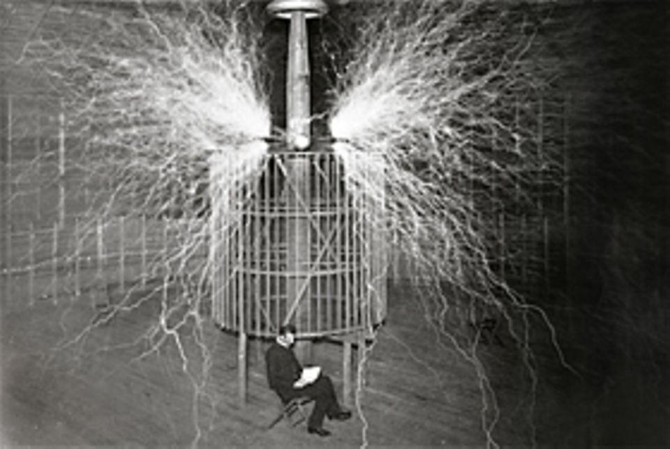 """Erfinder: Mit dieser Spulenkonstuktion erprobt Nikola Tesla 1899 unter spektakulären Entladungen, hervorgerufen durch Spannungen von mehr als zwölf Millionen Volt, ob sich Strom durch die Luft übertragen lässt: ähnlich wie Radiowellen. Auch wegen solcher Versuche nennen ihn Bewunderer """"Magier der Elektrizität"""". Doch selbst Tesla kann nur scheinbar - nämlich dank einer doppelten Belichtung - zwischen den Stromblitzen sitzen, ohne getötet zu werden"""