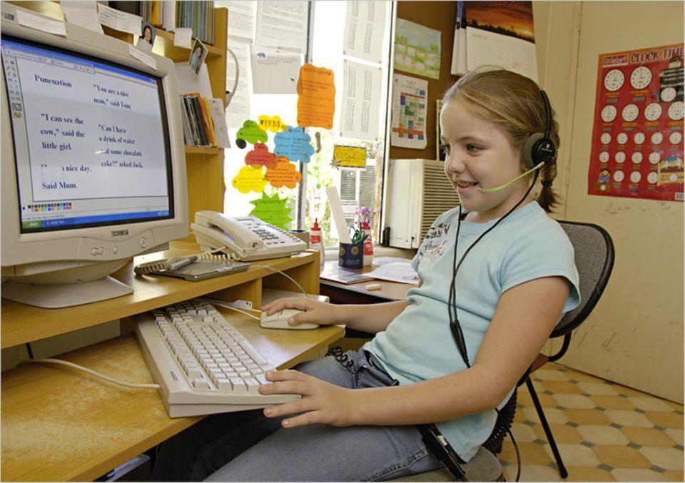 """Per Computer lockt sich Kirby bei der """"School of the Air"""" ein. Die Internetschule wurde für Kinder wie sie gegründet, die an abgelegenen Orten leben"""