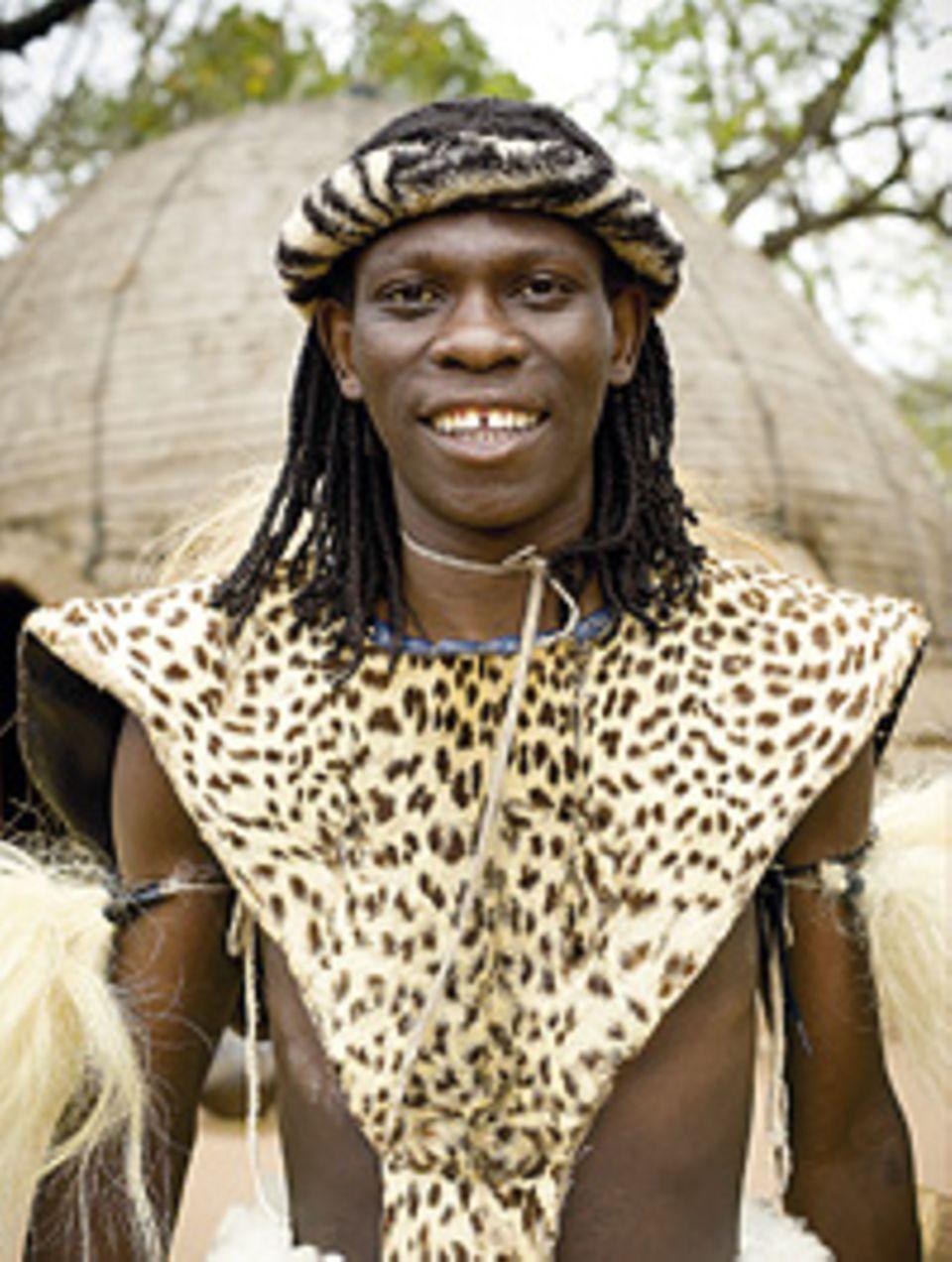 Südafrika: Ein Mann vom Zulu-Stamm zeigt Touristen seine traditionelle Tracht