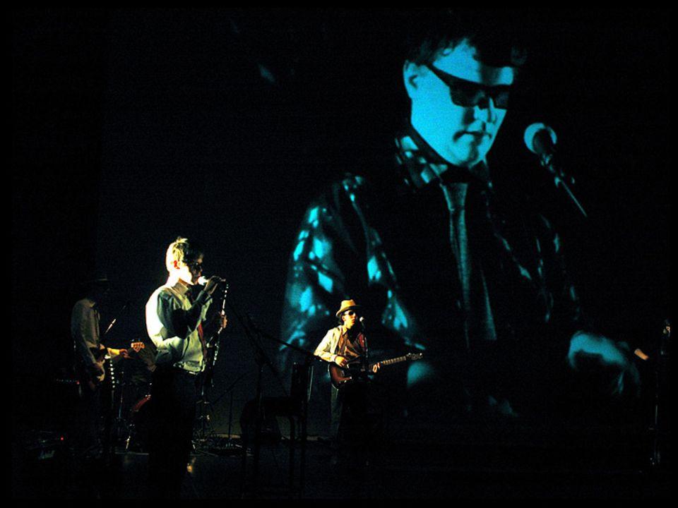 Ein Bandauftritt von kUNDEkÖNIG. Das Gesicht von Sänger Carsten Schnathorst ist auf eine riesige Leinwand projiziert