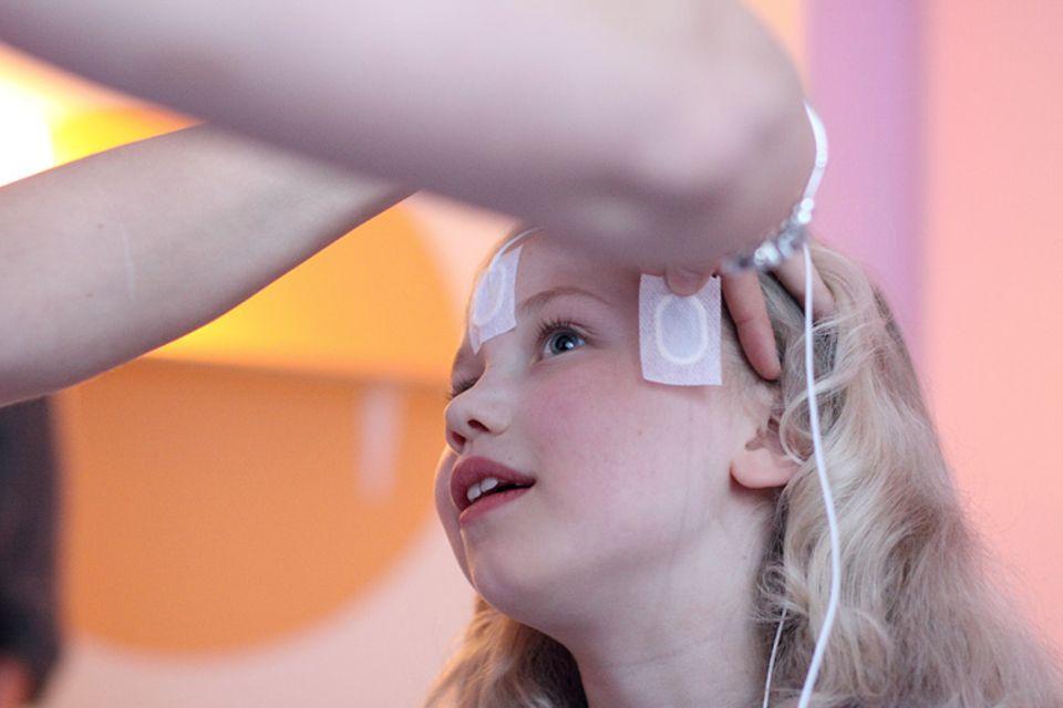 Forschung: Geduldig lässt sich Marilen einen der elf Sensoren an die Schläfe kleben