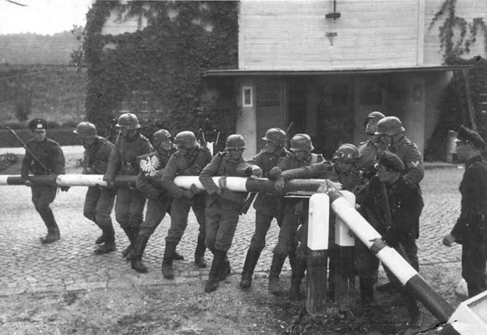 Während des Überfalls auf Polen im September 1939 demontieren deutsche Soldaten zahlreiche Schlagbäume an der 2300 Kilometer langen deutsch-polnischen Grenze. Die meisten dieser Bilder sind nachträglich für die Fotografen und Kameraleute der NS-Propaganda gestellt worden
