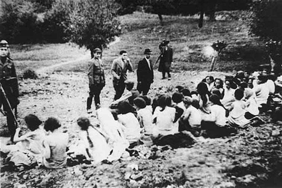 Deutsche Polizisten und Helfer in Zivil beaufsichtigen wie sich jüdische Frauen kurz vor ihrer Erschießung entkleiden. Von den ersten Kriegstagen an folgen der SS unterstellte Todeskommandos den Wehrmachtssoldaten auf ihrem Vormarsch gen Osten