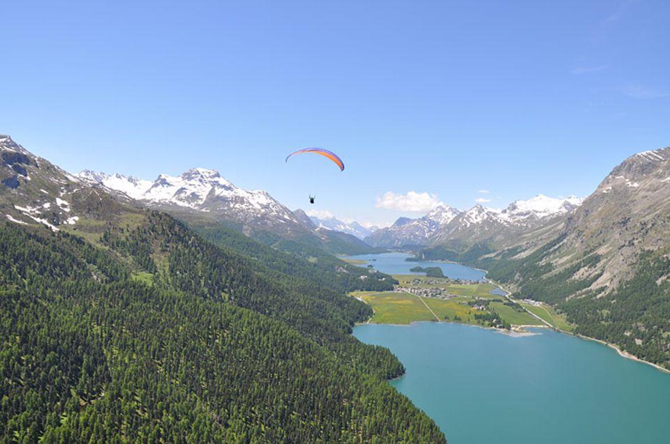 Den Gleitschirmfliegern über dem Silvaplaner See bietet sich ein atemberaubendes Panorama
