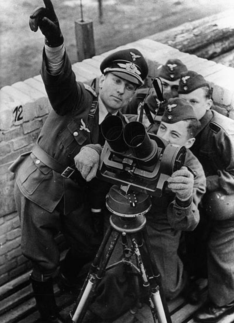 Ausbildung junger Luftwaffenhelfer durch einen Flakoffizier am Flakfernrohr 1943. Wie diese Jungen lernen auch Herbert Sauer und Rolf Schörken das Erkennen und Ansprechen anfliegender Flugzeuge