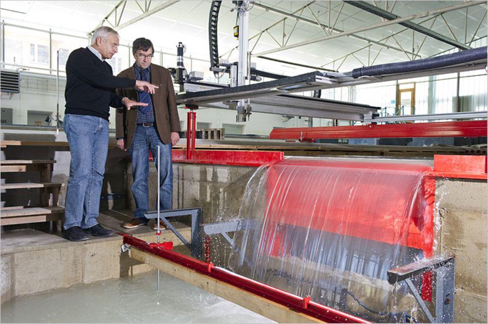 Wasserkraft: Peter Rutschmann (l.) und Albert Sepp am Modell des Kraftwerks. Eine Klappe im Wehr lässt Wasser - und damit auch Fische - passieren. Das Kraftwerk befindet sich in einer Kiste vor dem Wehr