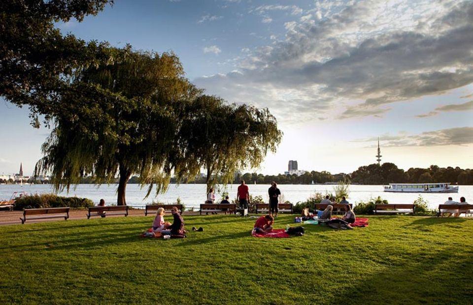 Umwelthauptstadt: Eine Wiese an der Außenalster lädt zum Picknick ein. Im Hintergrund, auf der anderen Seite der Alster ist Hamburgs Innenstadt zu erkennen