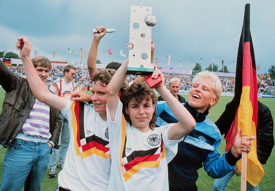 Fußballweltmeisterschaft: Siegerehrung bei der Europameisterschaft 1989. Die deutschen Frauen holen den Titel im eigenen Land. Darüber freuen sich: Jutta Nardenbach, Petra Damm und Doris Fischen mit Pokal