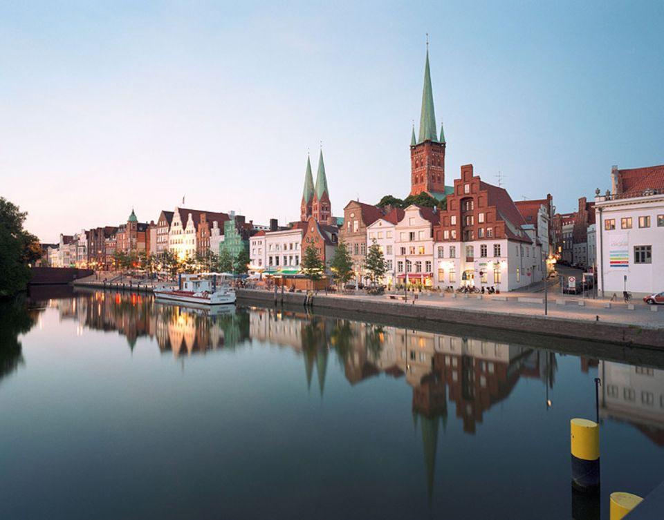 Städtereise: Historische Kaufmannshäuser stehen am Ufer der Trave, dahinter der Turm von St. Petri und die Doppelspitze der Marienkirche