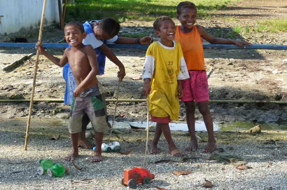 Kinder in Warimak spielen mit selbst gebastelten Autos aus Plastikflaschen