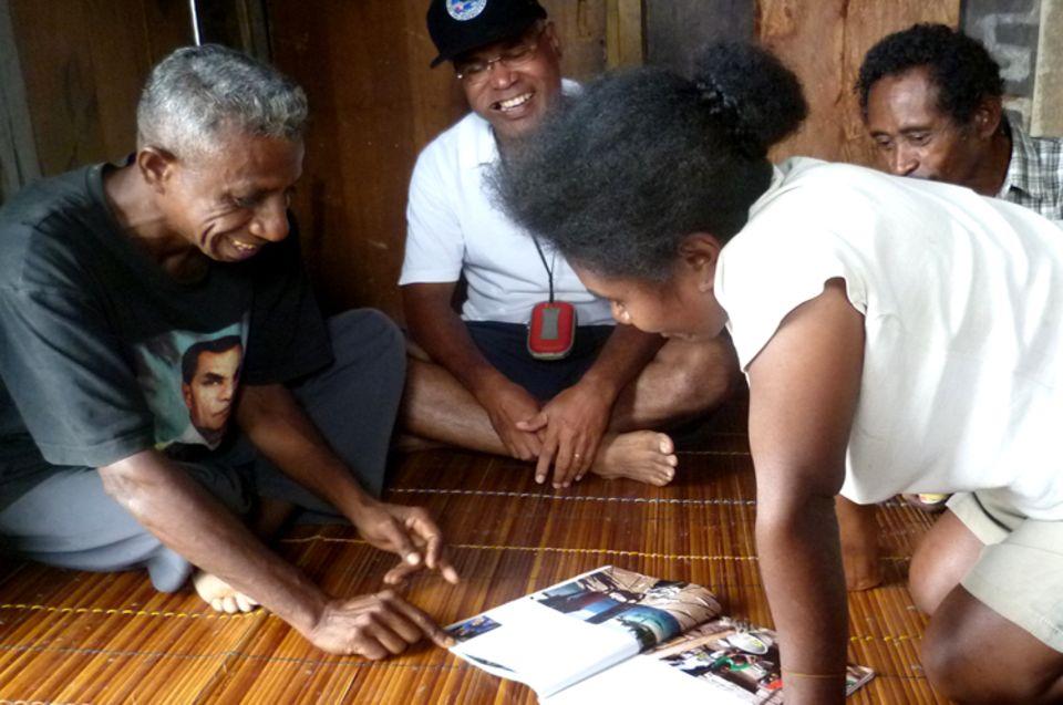 Bewohner von Kabilol sehen sich fasziniert die Bilder der Reportage von Lars Abromeit und Tim Laman (Fotos) in GEO an