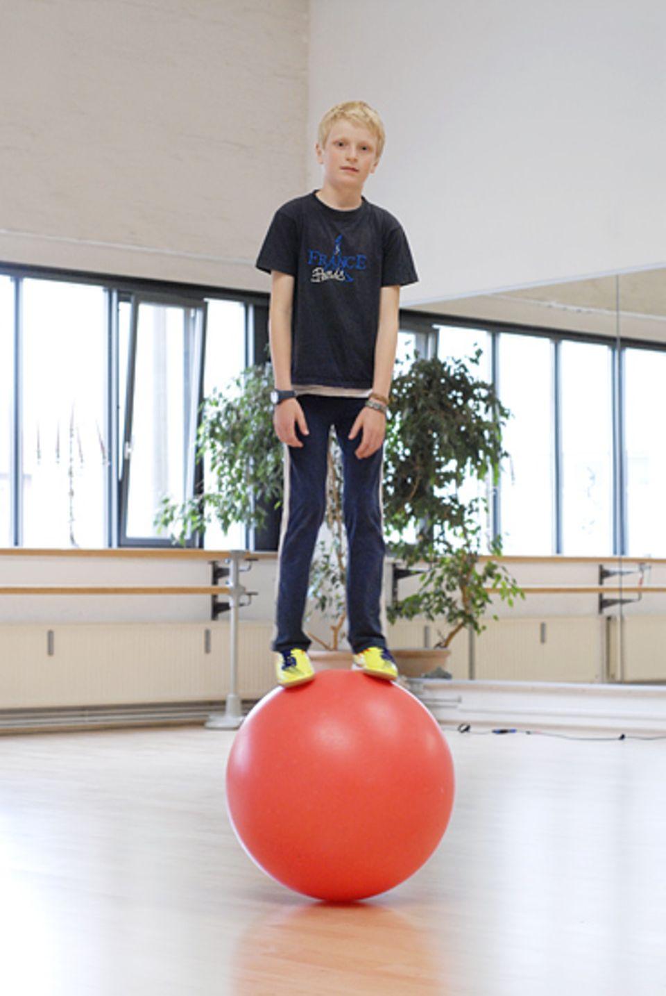 Zirkusschule: Als würde er von selbst daran haften: Iven auf der Laufkugel