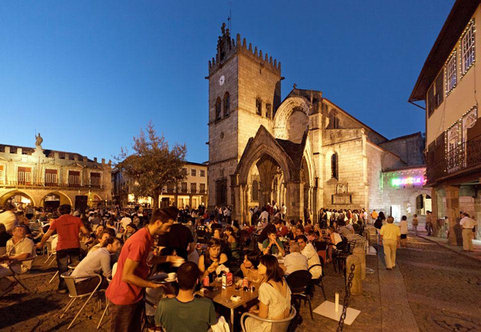 Städtereise: Sundowner mit Gottes Segen: Einheimische und Gäste lieben die Cafés vor der Igreja de Nossa Senhora da Oliveira in der Altstadt