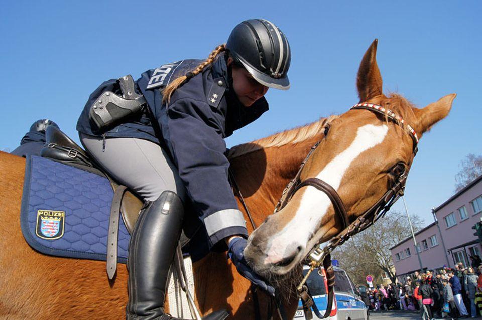 Hier seht ihr eine Polizeibeamtin der Reiterstaffel Frankfurt, die ihrem Pferd gerade ein Stück Zucker zur Belohnung gibt