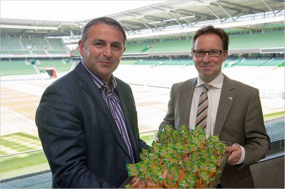 Bremen: Dr. Ingo Stryck (Geschäftsführer Marketing Wiesenhof) und Klaus Allofs (Geschäftsführer Werder Bremen) präsentieren vor der Wiesenhof-Loge stolz die Wiesenhof Spezialitäten