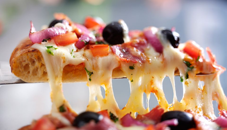 """Lebensmittelproduktion: Nicht jede in der Fabrik hergestellte Fertigpizza ist mit einem Belag aus echtem Käse bedeckt. Bei manchen handelt es sich um """"Analogkäse"""" - ein Imitat aus Pflanzenfetten"""