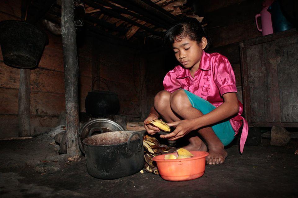 Yeni macht Frühstück für ihre Familie: Wie jeden Tag gibt es Kochbananen und Kokosnuss