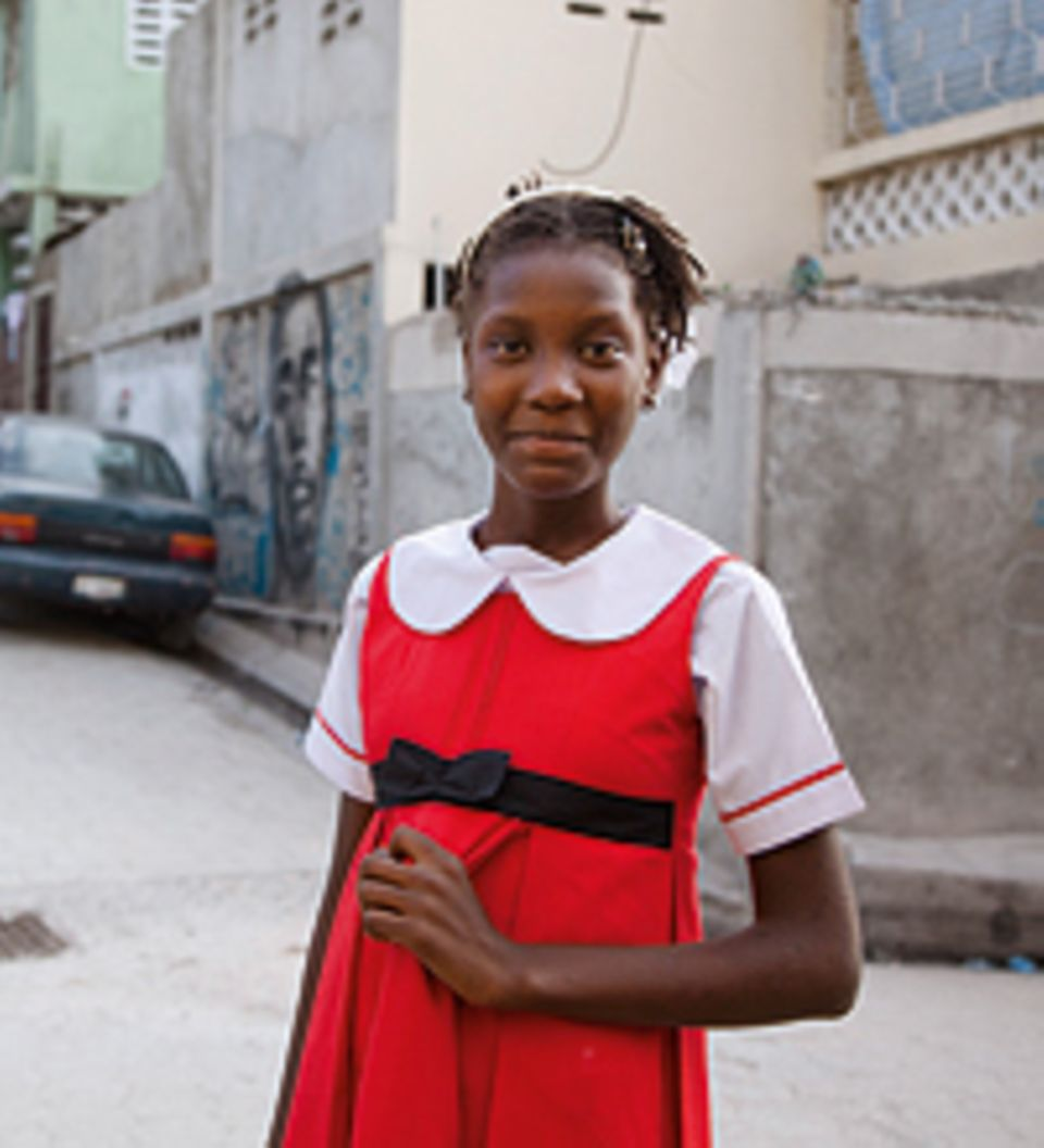 Landa lächelt: In ihrer Straße in Port-au-Prince posiert sie in ihrem Lieblingskleid. Nach dem schweren Beben 2010 lag in der Stadt kaum ein Stein mehr auf dem anderen. Die meisten Häuser waren zerstört