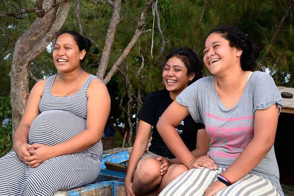Seni und Muna Moala und eine ihrer Cousinen beim allabendlichen Singen und Geschichten erzählen an der Küste von Patangata, Tongatapu, Tonga