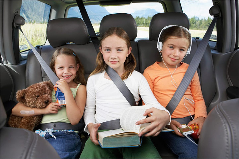 Auto fahren: Zu dritt auf der Rückbank kann beim Autofahren ganz schön langweilig sein. Dann ist gute Unterhaltung gefragt!