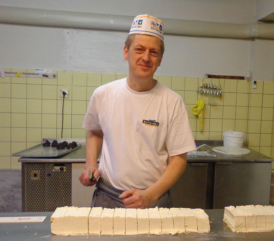 Beruf: Norbert Umbach in voller Montur: mit weißer Mütze, Schürze und schwarz-weiß-karierter Hose