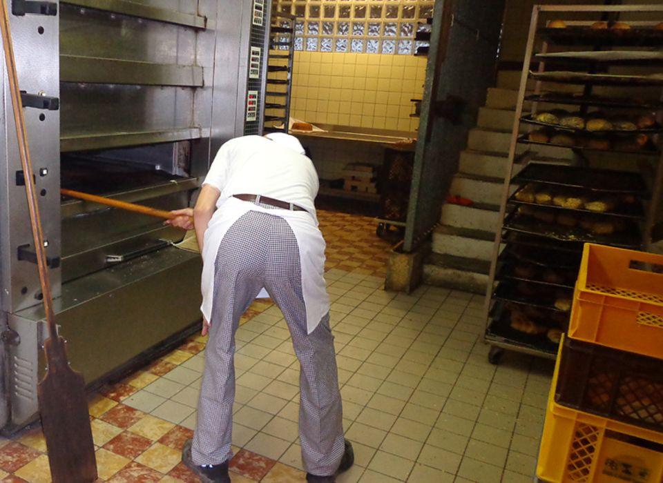 Beruf: Mit beiden Händen greift Umbach gerade nach dem großen Schieber, öffnet die Klappe des Ofens und hebt schwungvoll ein Blech frischer Brötchen heraus. Es riecht lecker