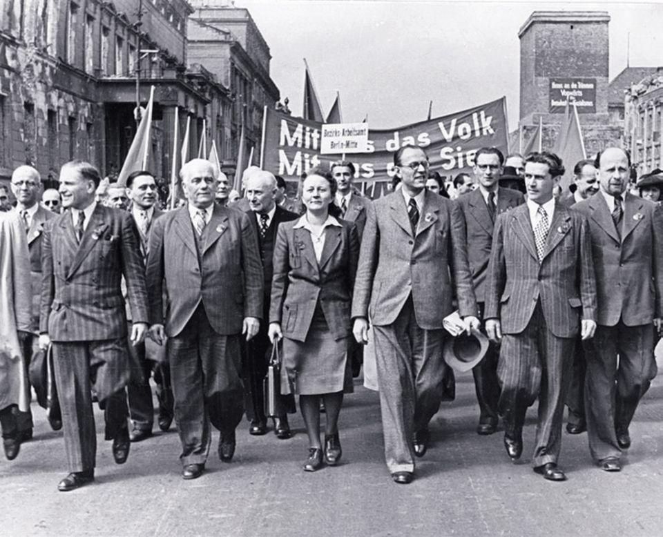 1949: Gründung der DDR: Der frühere SPDler Otto Grotewohl (mit Hut) und der weißhaarige Kommunist Wilhelm Pieck führen offiziell die neue SED
