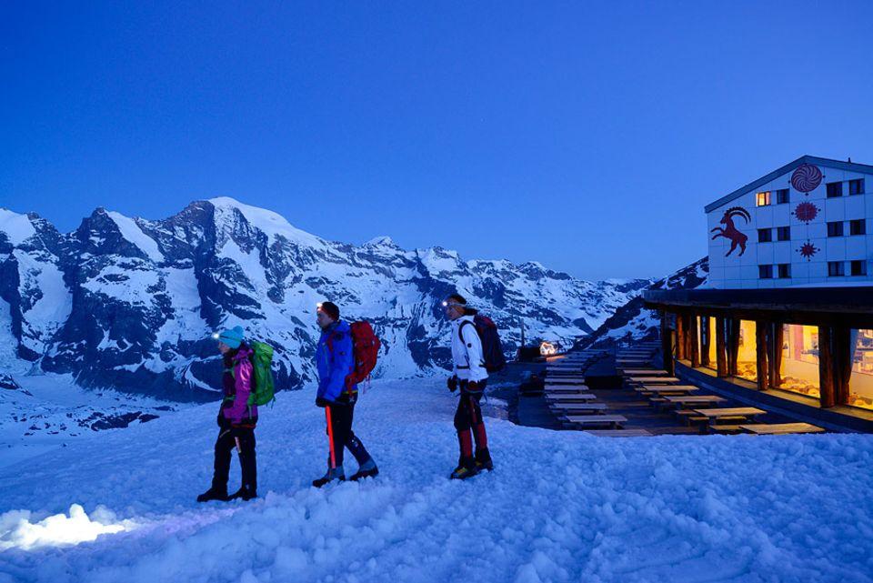 Almhütten: Drei Bergsteiger starten von beleuchtetem Gasthaus Diavolezza zum Piz Palü in Graubünden