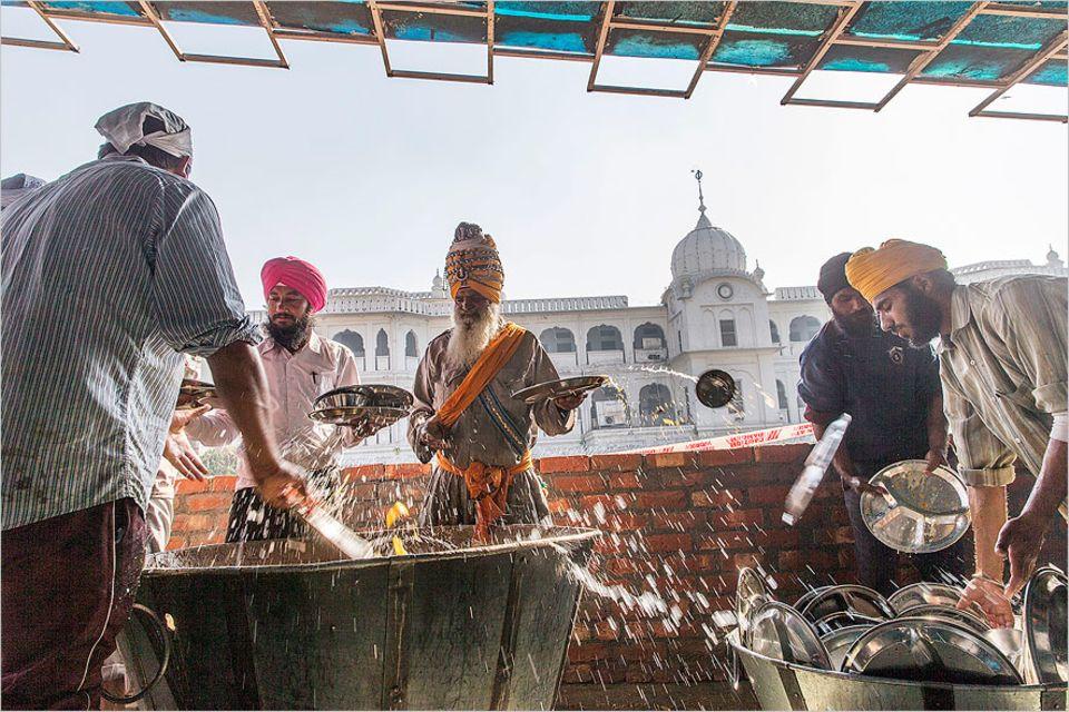 Indien: Spülen für das Karma. In der Waschstraße des Tempels werden die Teller vorgespült