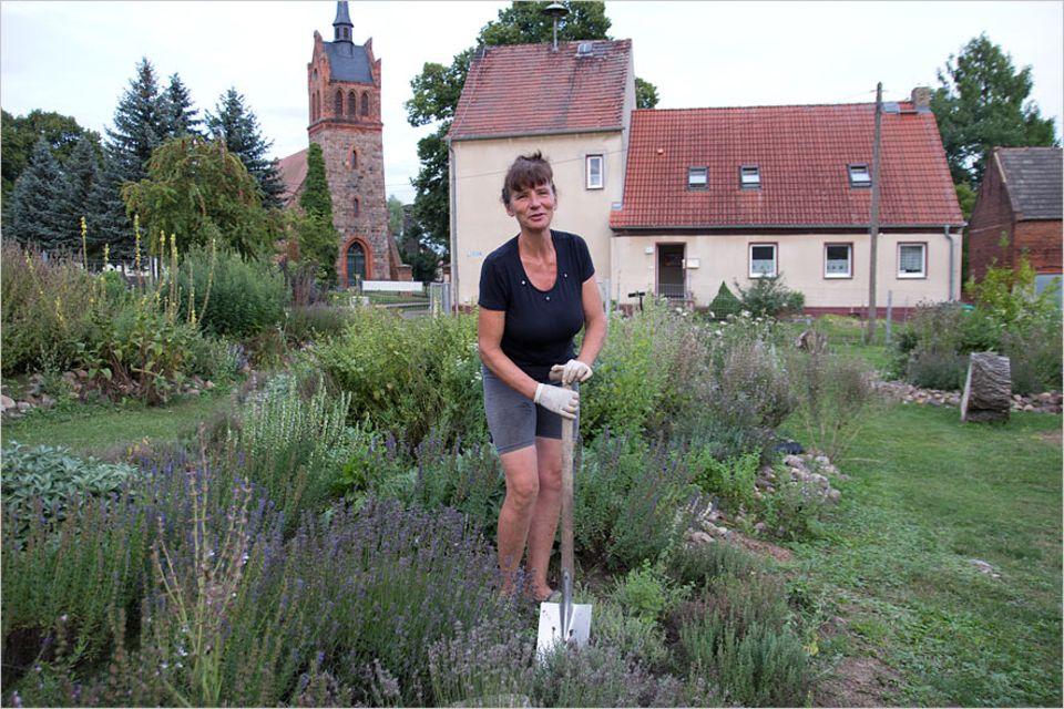 """Stellplatzführer """"Landvergnügen"""": Bei der Arbeit! Kerstin Weiße in ihrem Gesundheitsgarten. Sie gräbt um und ein, während Campingbus-Besitzer zwischen Blumen, Kräutern und Wildpflanzen wandeln"""