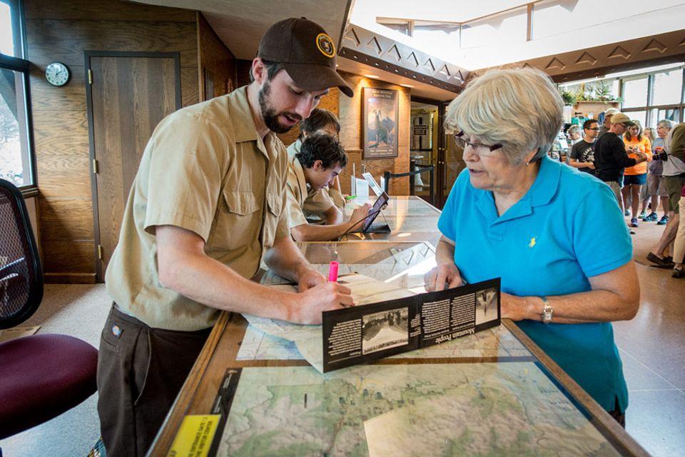 Rocky Mountains Nationalpark: Ein Ranger markiert auf einer Landkarte für eine Besucherin empfohlene Haltepunkte im Rocky Mountain Nationalpark