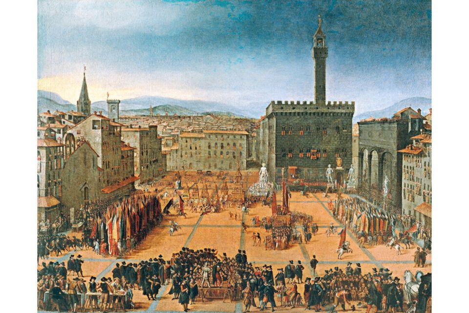 Florenz um 1300: Mit mehr als 90.000 Einwohnern gehört Florenz um 1300 zu den größten Städten Europas. Tuchhersteller, Händler und Bankiers sorgen für eine Geschäftigkeit, in der der Kapitalismus zum ersten Mal aufblüht. Die neue Elite zeigt ihren Wohlstand mit Prachtbauten wie dem 1314 vollendeten Palazzo della Signoria (heute Palazzo Vecchio, hinten rechts), dem Sitz der Stadtregierung, vor dem sich hier Menschen zu einem Festumzug versammelt haben