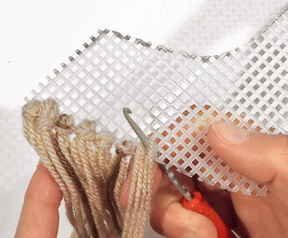 Verkleiden: Nutzt die Häkelnadel, um die losen Fadenenden stramm zu ziehen
